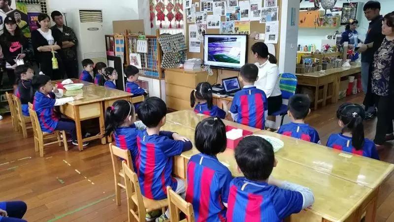 为了在幼儿园广泛营造浓郁的足球氛围,幼儿园的每个班级都组建了一个足球角,选择一所足球俱乐部,利用俱乐部的元素来布置班级环境。老师们发动班级里的球迷家长收集了足球俱乐部的旗帜、徽章、服装、球星图片、球星玩偶等物品,所有的孩子和家长一起对教室进行了装扮,还收集制作了介绍本班足球俱乐部信息的小海报,一时间十四个班摇身一变成了十四个小小足球俱乐部。孩子们制作我的应援棒,一起想足球标语牌,跟大家介绍自己支持的球队和喜欢的球星,全身心地感受足球带来的乐趣。